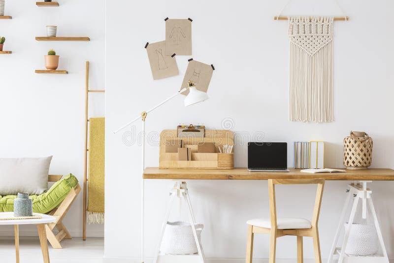 Cadeira de madeira na mesa com portátil e organizador no interior branco do escritório domiciliário com decoração foto de stock