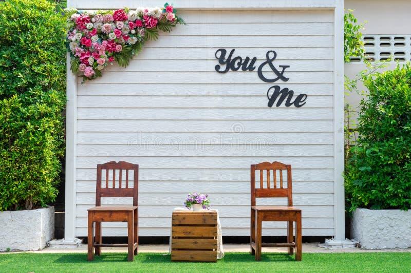 Cadeira de madeira no parque colocado ao longo da parede da ?rvore O sol est? brilhando para baixo na cadeira O jardim é baseado  foto de stock royalty free