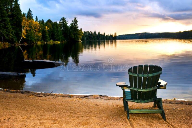 Cadeira de madeira no por do sol na praia fotografia de stock royalty free