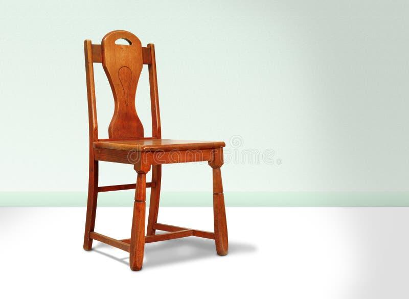 Cadeira de madeira vermelha antiga de encontro a uma parede verde imagem de stock royalty free