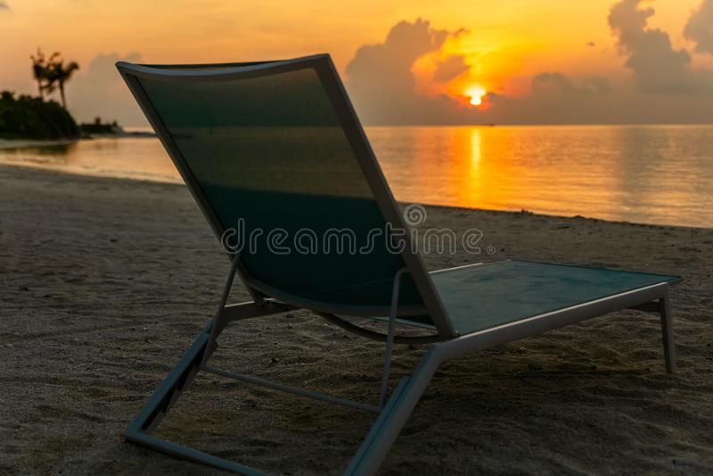 Cadeira de praia confortável na sapata só do mar no tempo do por do sol foto de stock royalty free