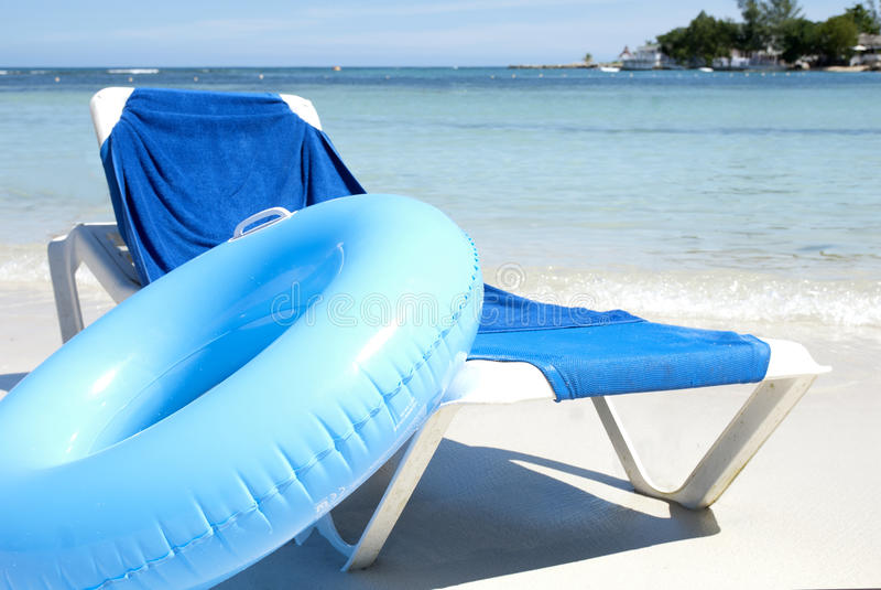 Cadeira de praia e câmara de ar da água imagens de stock