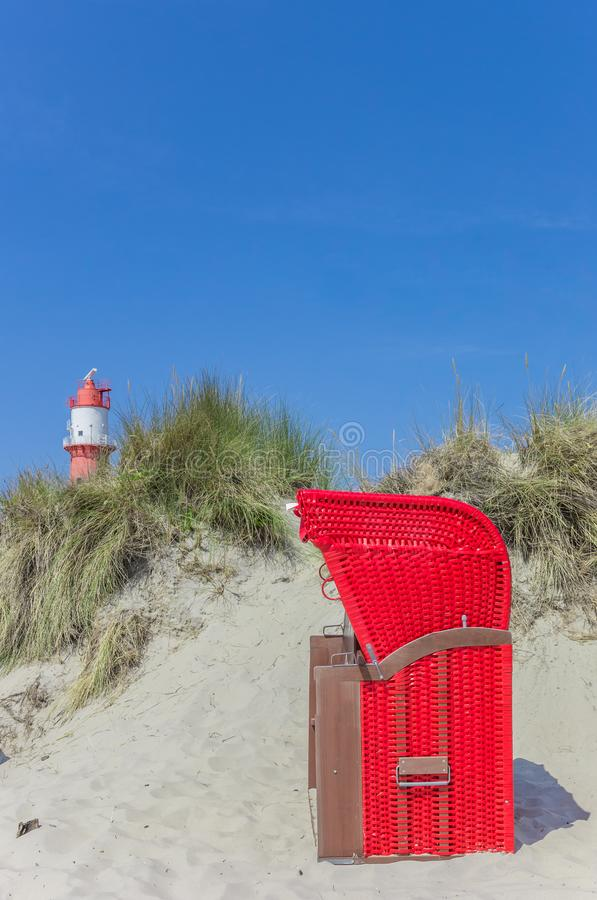 Cadeira de praia vermelha tradicional nas dunas de Borkum imagem de stock