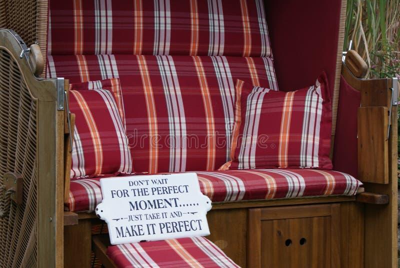 A cadeira de praia de vime telhada com os coxins quadriculado vermelhos está esperando o convidado do feriado fotos de stock royalty free