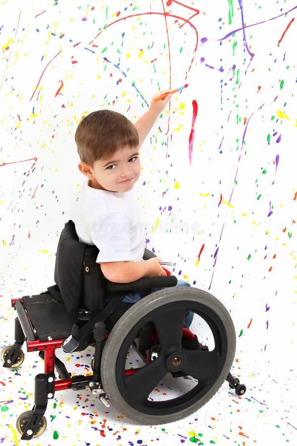 Cadeira de rodas da pintura da criança do menino fotografia de stock royalty free