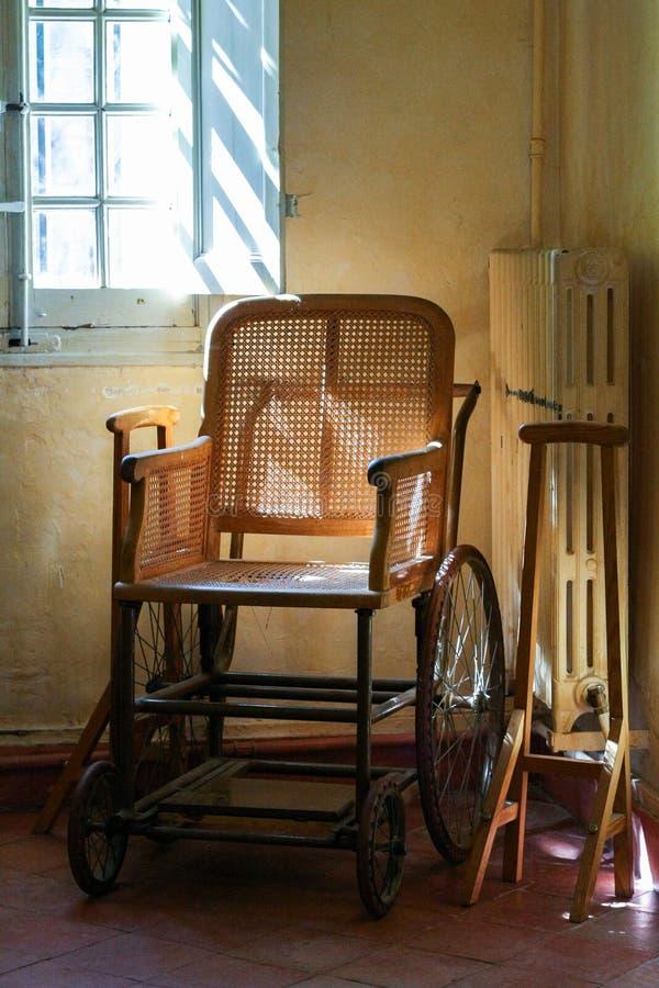 Cadeira de rodas de madeira velha no interior foto de stock