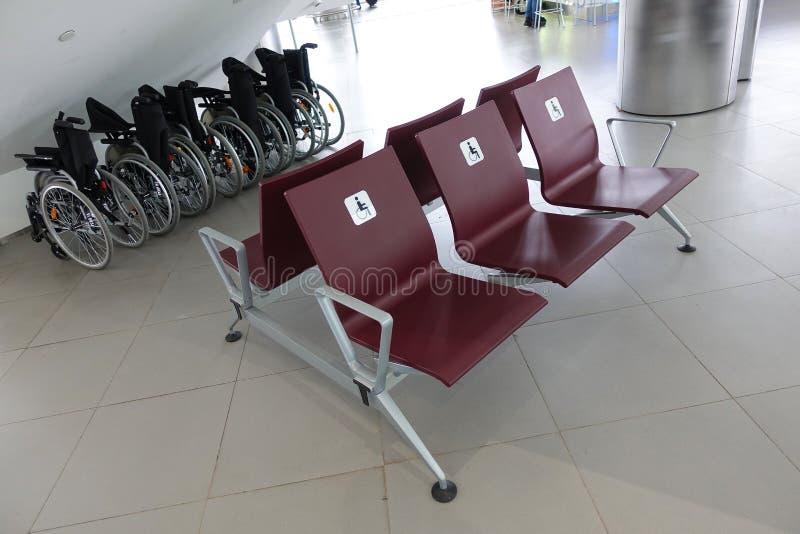 Cadeira de rodas na construção do aeroporto Inquietação com povos com inabilidades imagem de stock