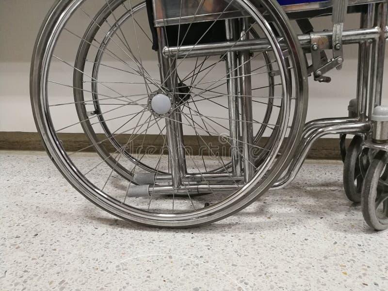 A cadeira de rodas para a pessoa doente é feita de Stanhae, estacionado no lado da parede da sala de hospital fotografia de stock royalty free
