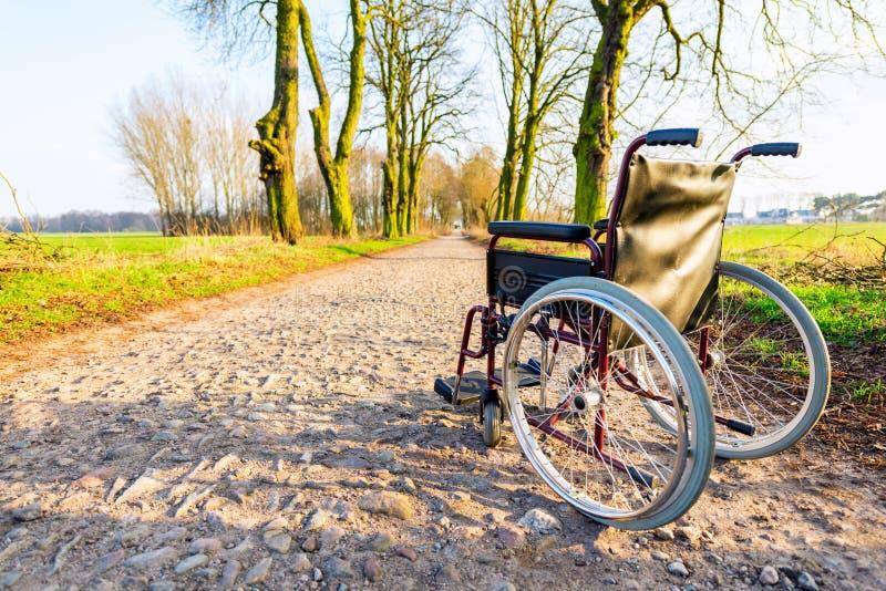 Cadeira de rodas vazia na estrada do campo no por do sol fotografia de stock royalty free