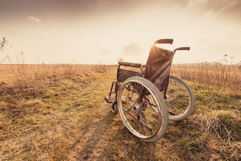 Cadeira de rodas vazia no prado no por do sol - versão retro do vintage foto de stock