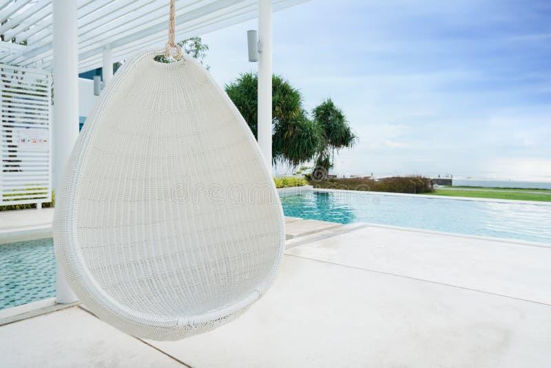Cadeira de suspensão de relaxamento do rattan branco na piscina na opinião do mar imagem de stock