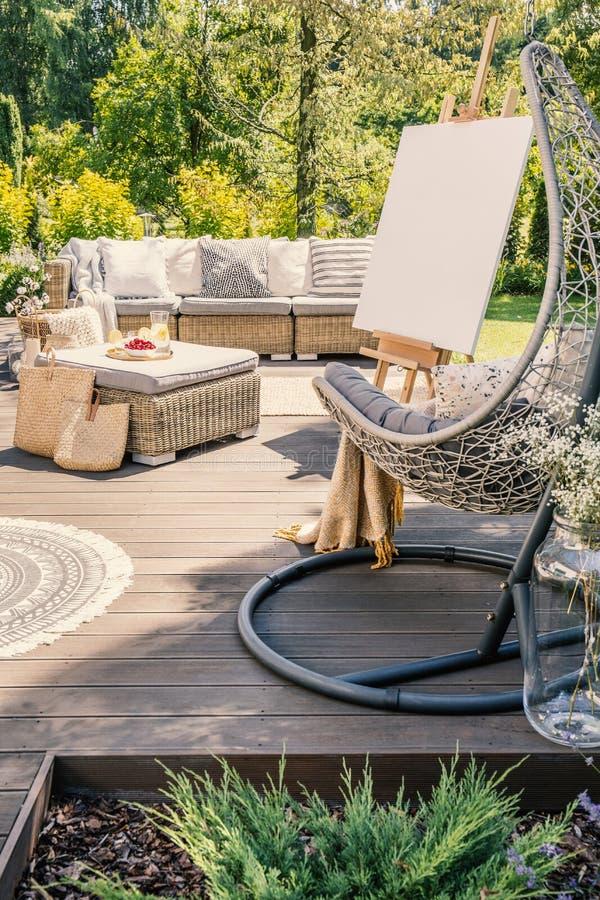 Cadeira de suspensão no pátio de madeira com a tabela da armação e do rattan na frente do sofá no jardim imagens de stock
