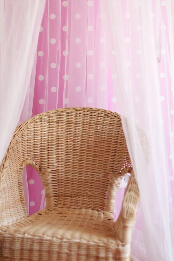 A cadeira de vime criançola pequena está ao lado da parede cor-de-rosa imagem de stock