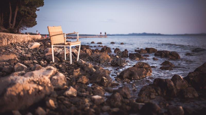 Cadeira de vime na praia rochosa durante o por do sol imagem de stock