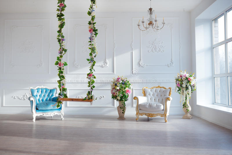A cadeira do estilo do vintage do couro branco na sala interior clássica com janela e mola grandes floresce fotos de stock royalty free
