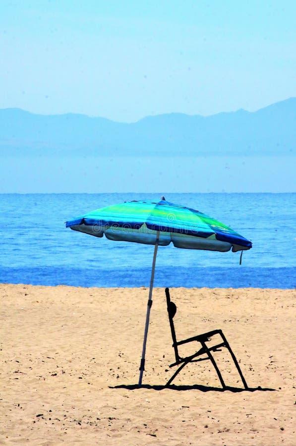 Cadeira do guarda-chuva e de praia na praia em Califórnia central fotografia de stock