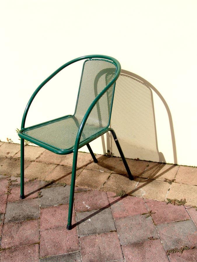 Cadeira do metal no sol fotografia de stock royalty free
