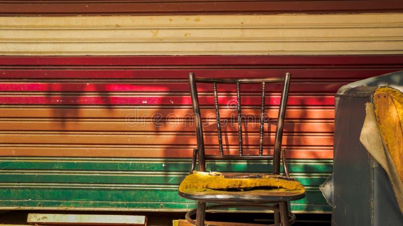 Cadeira do metal do vintage e sofá abandonados do sofá com rolo colorido fotos de stock royalty free