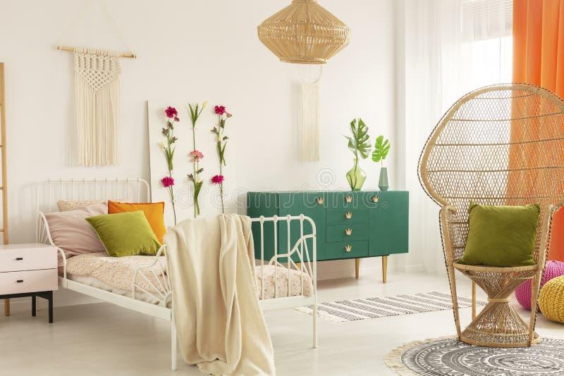 Cadeira do pavão com o descanso do verde azeitona no quarto trendsetting interior com a cama do metal branco com descansos colori fotografia de stock