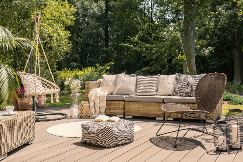Cadeira do pufe e do rattan no pátio de madeira com o canapé no jardim durante o verão Foto real fotos de stock royalty free