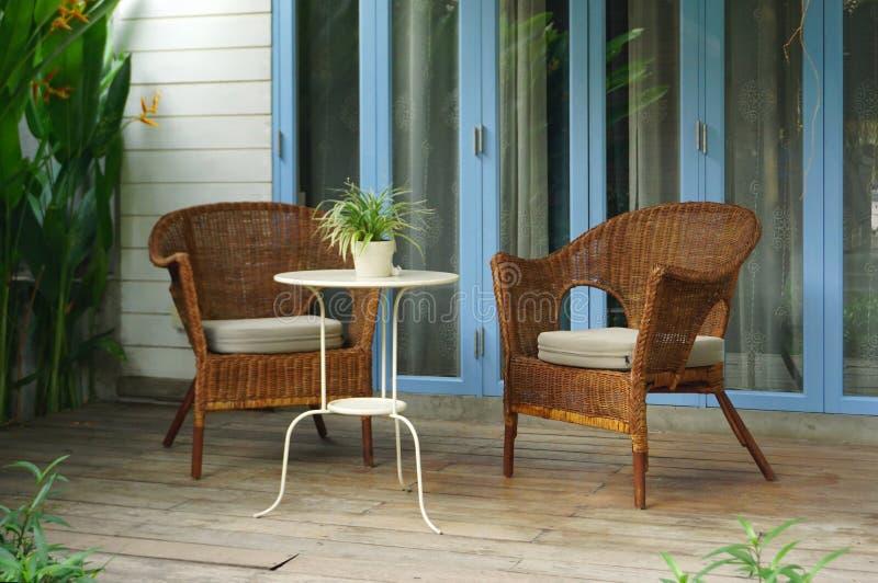 Cadeira do rattan do vintage com a mesa de centro no pátio foto de stock royalty free