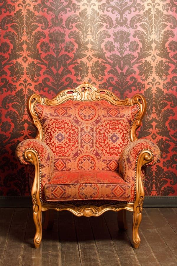 Cadeira do vintage com acentos do ouro ao lado da parede fotos de stock royalty free