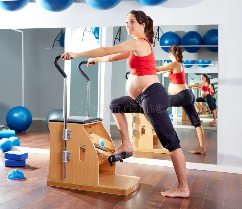 Cadeira do wunda do exercício dos pilates da mulher gravida imagens de stock