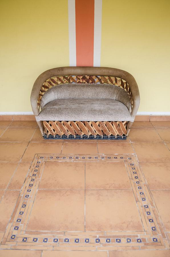 Cadeira dobro feita da madeira com coxins marrons em um assoalho de tons marrons em um corredor de uma casa imagem de stock royalty free