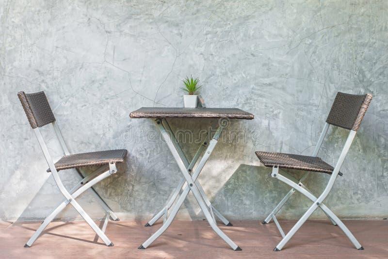 Cadeira e tabela na parede de madeira do pátio e do sótão no fundo imagens de stock