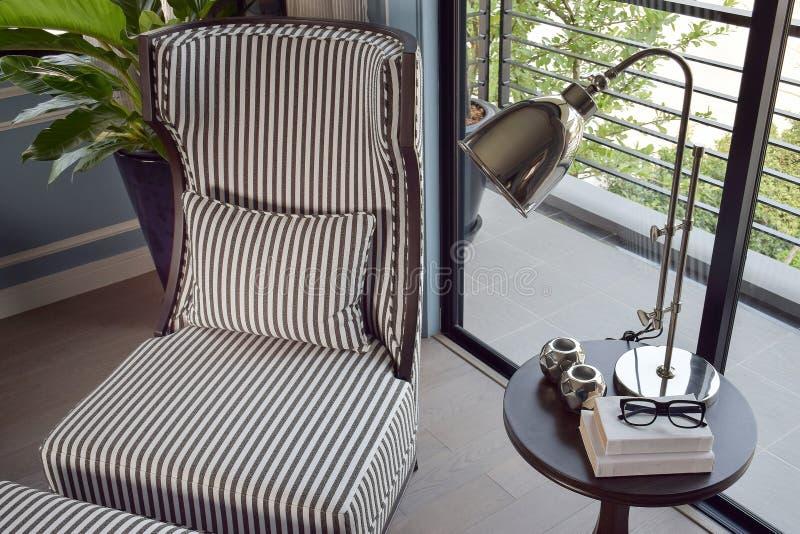 Cadeira fácil listrada preta no canto com a lâmpada de bronze decorativa foto de stock royalty free