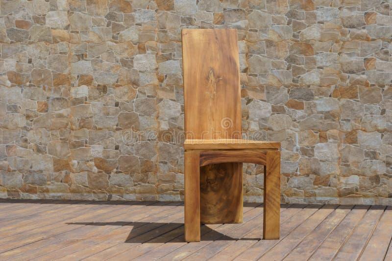 Cadeira feita da madeira maciça em um fundo de pedra imagem de stock