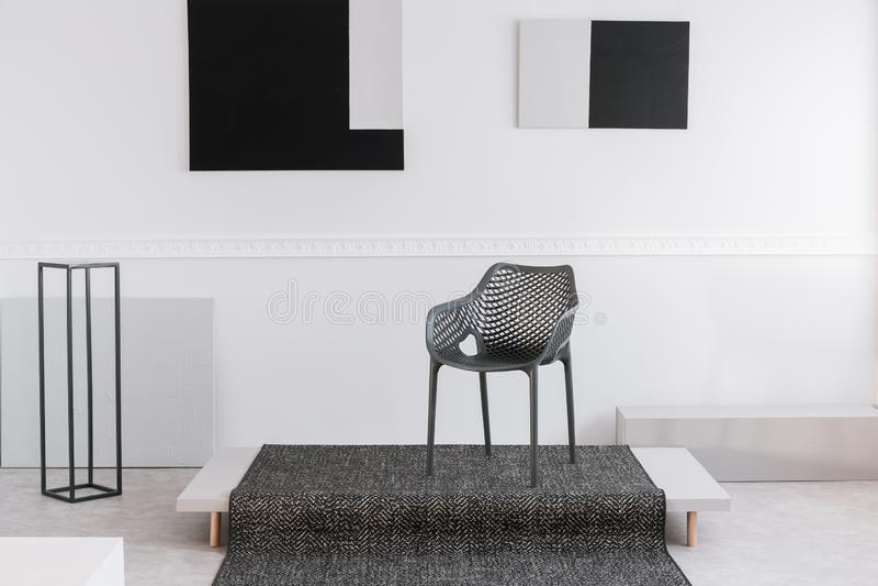 Cadeira industrial preta elegante no meio do interior monocromático imagens de stock royalty free