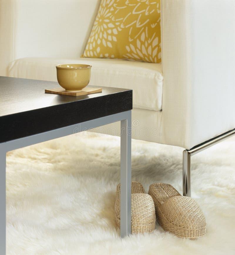 Cadeira interior da mobília da decoração da sala de visitas contemporânea, moderna, tabela com xícara de chá e deslizadores no ta imagens de stock royalty free