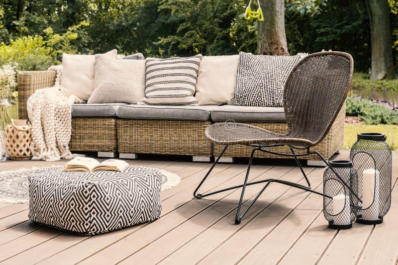 Cadeira modelada do pufe e do rattan no pátio de madeira com descansos sobre imagens de stock royalty free