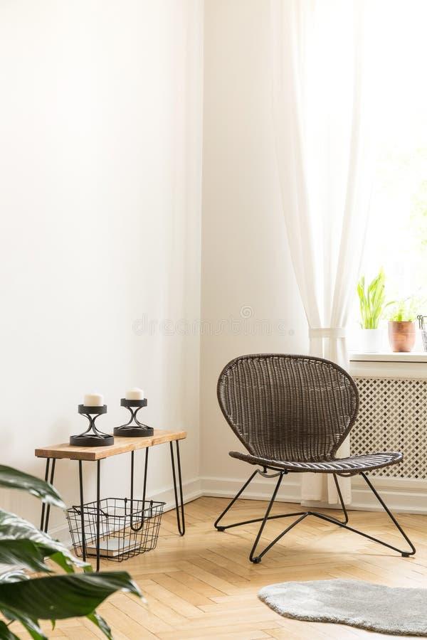 A cadeira moderna ao lado de uma tabela com velas nos suportes ajustou-se em um ro fotos de stock