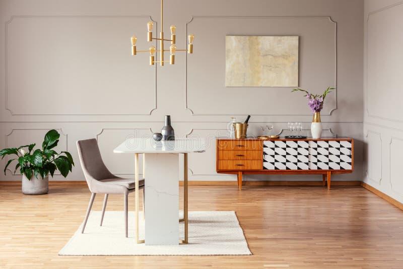 Cadeira na tabela sob a lâmpada do ouro no interior da sala de visitas com o cartaz acima do armário com planta Foto real foto de stock