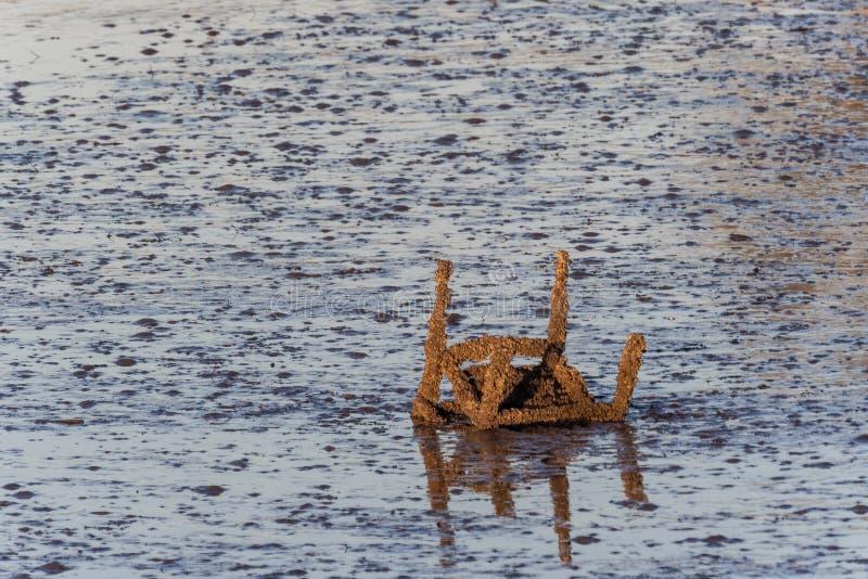 Cadeira oxidada exposta na maré baixa imagem de stock royalty free