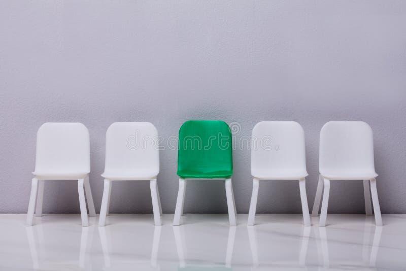 Cadeira pequena vazia na fileira em Grey Background foto de stock