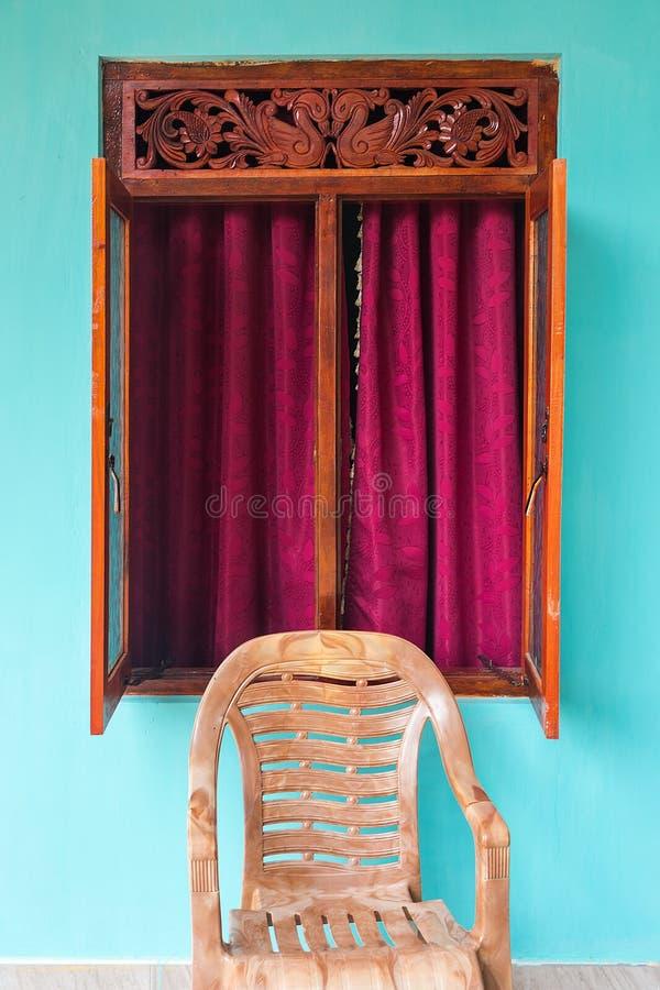 Cadeira plástica na frente da janela aberta fotos de stock royalty free