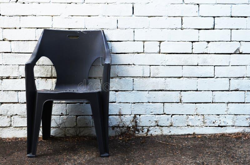 Cadeira pl?stica velha contra a parede imagem de stock