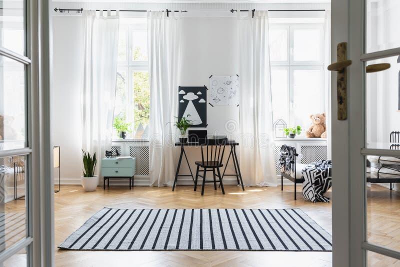 Cadeira preta na mesa no interior da sala de criança com janelas, cama e plantas Foto real foto de stock