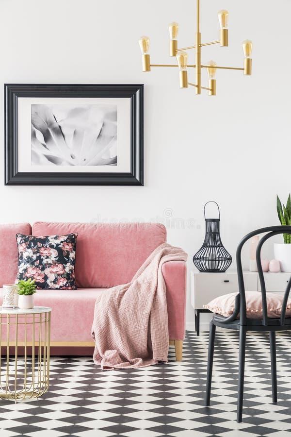 Cadeira preta perto do sofá cor-de-rosa no interior moderno da sala de visitas com a lâmpada do cartaz e do ouro Foto real foto de stock