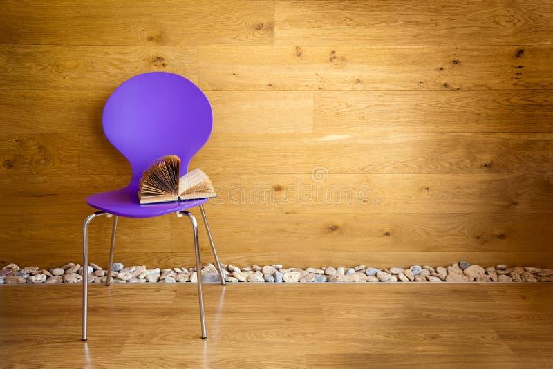 Cadeira roxa com a parede de madeira seguinte aberta do livro imagem de stock royalty free