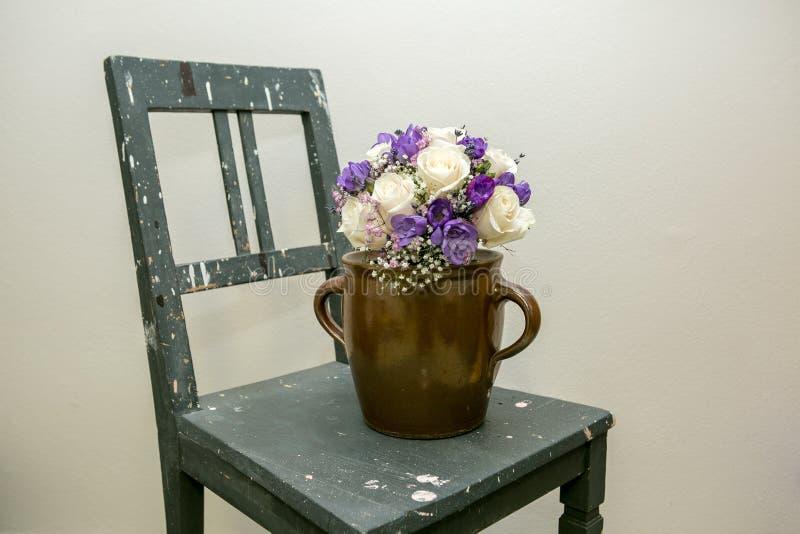Cadeira velha com flores brancas e violetas fotografia de stock