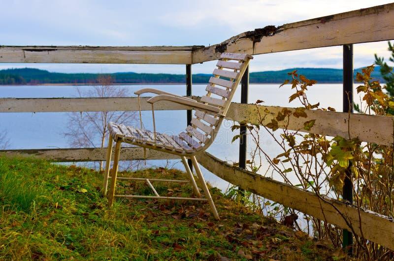 Cadeira velha em um lago foto de stock