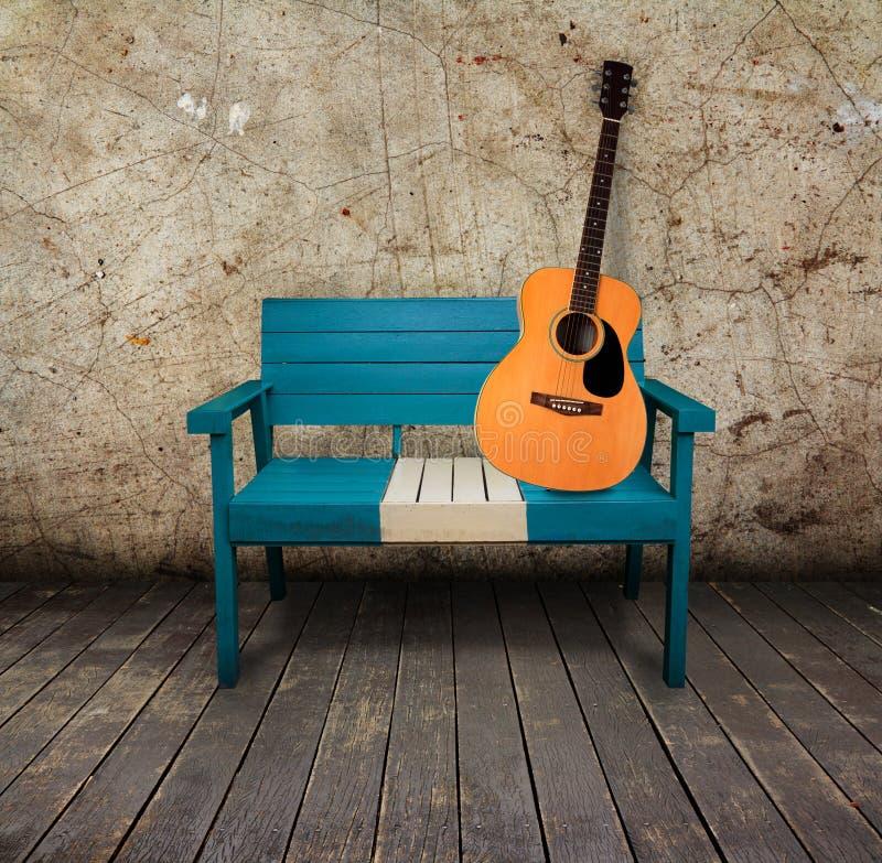 Cadeira verde e guitarra acústica em um quarto do grunge imagens de stock