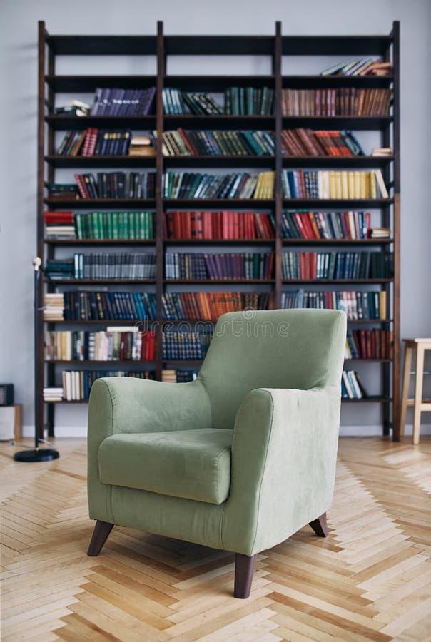 Cadeira verde no interior Biblioteca com os livros velhos nas prateleiras Livros em um armário de madeira velho imagens de stock royalty free