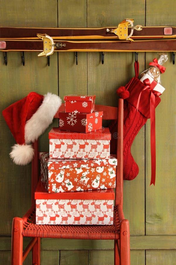 Cadeira vermelha com presentes de época natalícia fotografia de stock royalty free