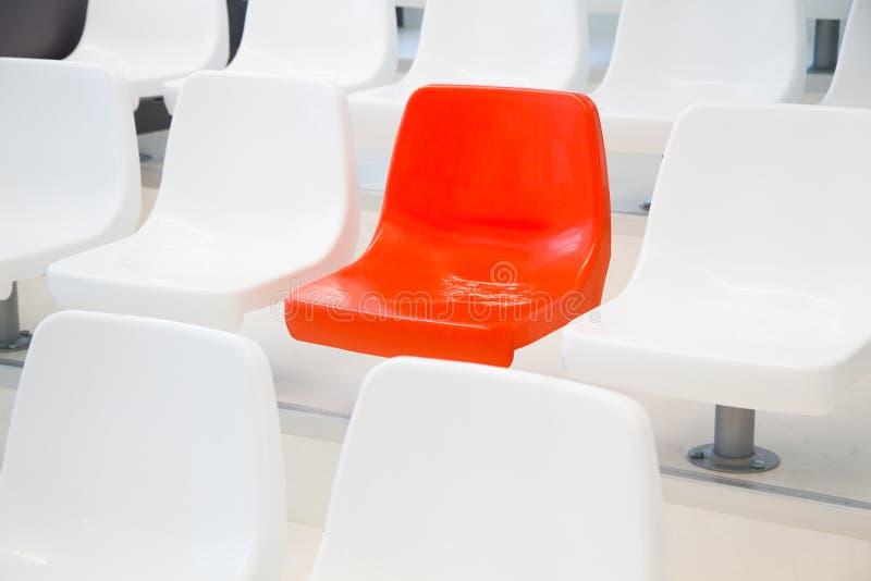 Cadeira vermelha entre o branco fotos de stock royalty free