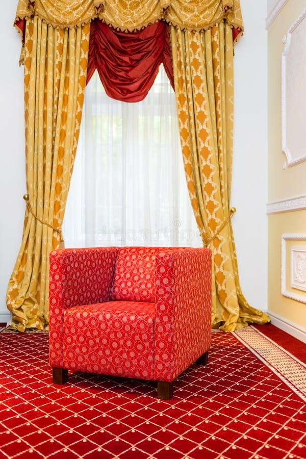 A cadeira vermelha na sala com tapete vermelho do vintage e amarelo clássico drapeja foto de stock royalty free